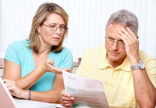 Senior couple puzzling over document
